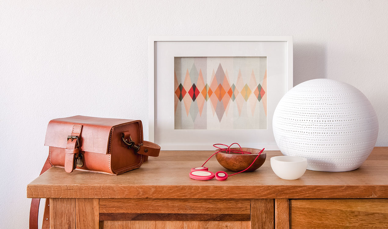 Indie styled product selection with leather bag, framed print, resin necklace, bowls and ceramic lamp.